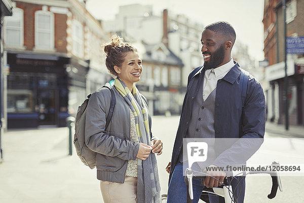 Lächelndes Paar  das mit dem Fahrrad auf einer sonnigen Stadtstraße pendelt.