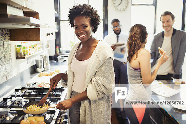 Portrait lächelnde Frau beim Kochen von Rühreiern am Herd in der Küche