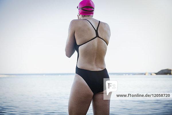 Weibliche Freiwasserschwimmerin beim Waten in der Meeresbrandung