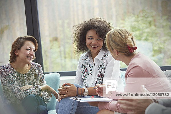 Smiling women talking in group therapy session