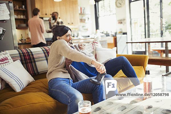 Verspielte Frau beim Videospiel auf dem Wohnzimmersofa