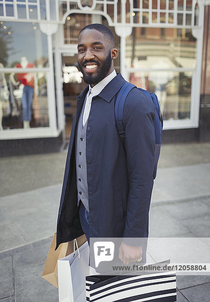 Portrait smiling  confident young man with shopping bags outside storefront