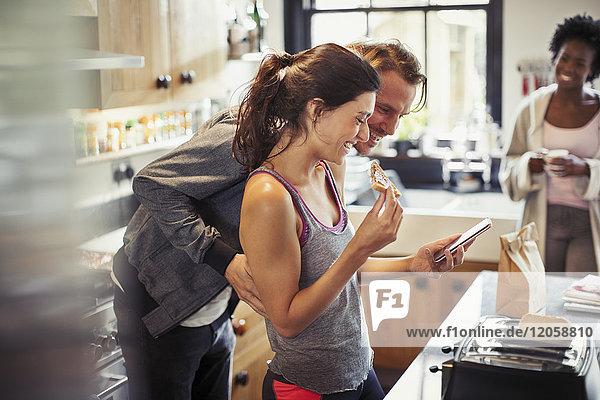 Lächelndes Paar SMS mit Smartphone  Toast essen in der Küche