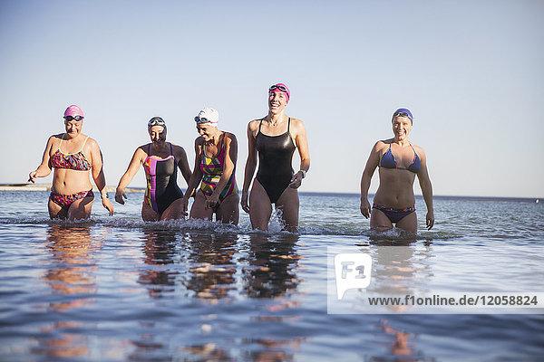 Lächelnde Schwimmerinnen  die in der Brandung waten.