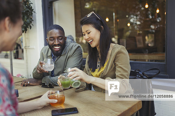 Lächelnde junge Freunde trinken Saft im Straßencafé