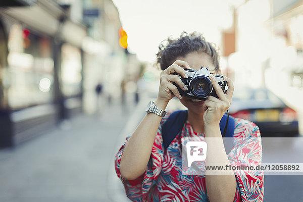 Portrait junge Frau beim Fotografieren mit Kamera auf der Straße