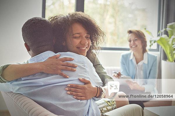 Lächelnde Therapeutin beim Umarmen von Paaren in der Paartherapie