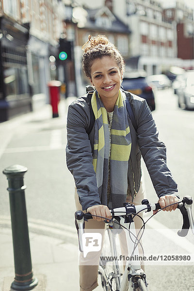 Portrait smiling young woman commuting  riding bicycle on sunny urban street