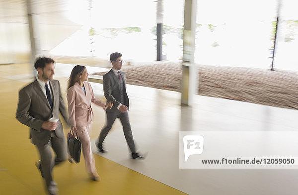 Geschäftsleute  die in der Bürolobby spazieren gehen