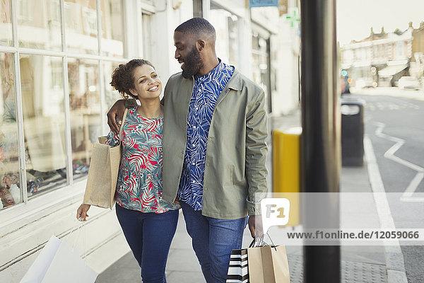 Zärtliches junges Paar mit Einkaufstaschen  die entlang der urbanen Schaufensterfront gehen.