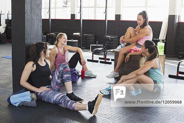 Junge Frauen beim Sprechen und Ausruhen im Fitnessstudio