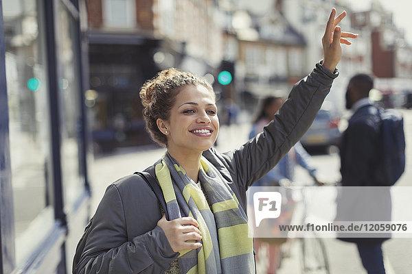 Lächelnde junge Frau  die ein Taxi auf einer sonnigen  städtischen Straße ruft.