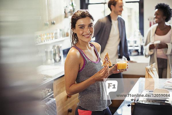 Portrait lächelnde junge Frau isst Toast und trinkt Orangensaft in der Küche