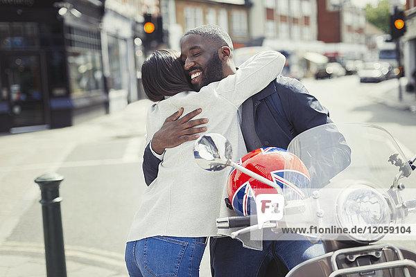 Zärtliches junges Paar  das sich am Motorroller auf der sonnigen Stadtstraße umarmt.