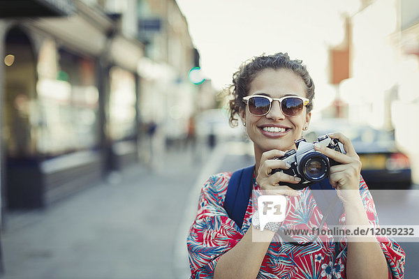 Portrait smiling young female tourist in sunglasses photographing with camera on urban street