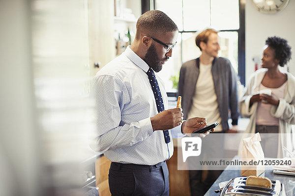 Geschäftsmann beim Frühstücken und SMSen mit Smartphone in der Küche