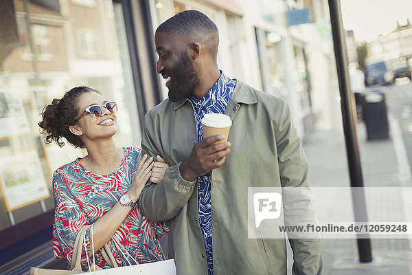 Smiling young couple with coffee walking arm in arm along storefronts