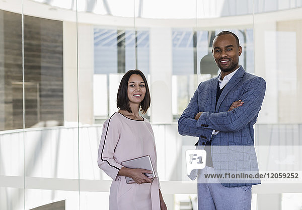 Portrait smiling  confident business people at office window