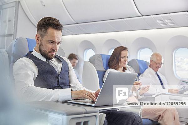 Geschäftsmann bei der Arbeit am Laptop im Flugzeug