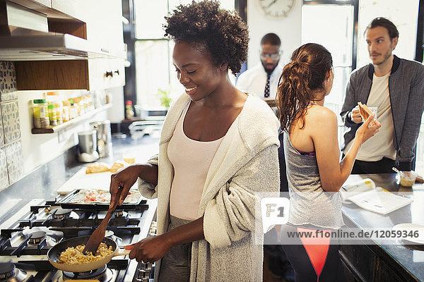 Frau kocht Rührei am Herd in der Küche