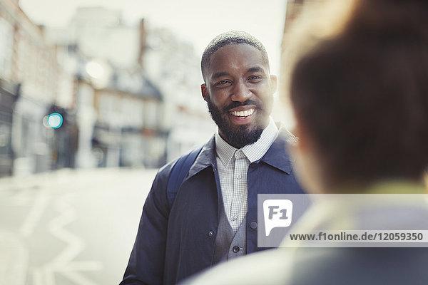 Lächelnder Geschäftsmann im Gespräch mit einem Freund auf einer sonnigen Stadtstraße