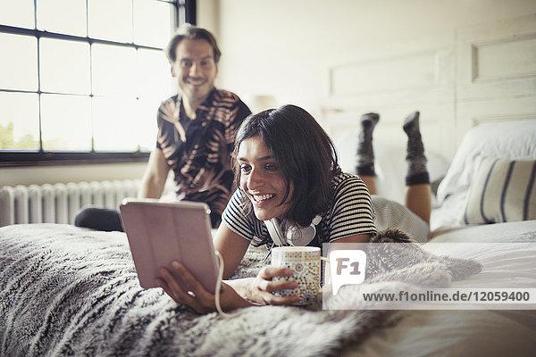 Lächelndes Paar  das sich entspannt  Kaffee trinkt und digitale Tabletten auf dem Bett benutzt.