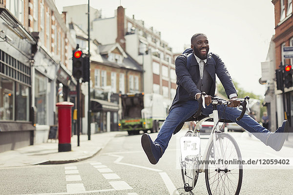 Playful young businessman commuting  riding bicycle on urban street