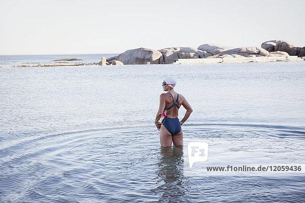 Weibliche Freiwasserschwimmerin stehend  im Meer watend
