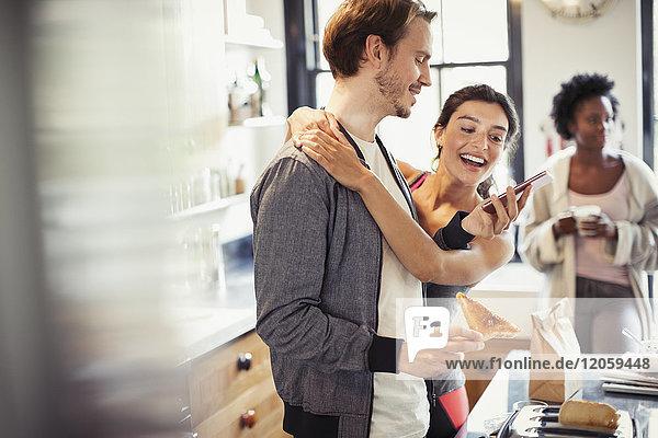 Zärtliche Paarumarmung  SMS mit Smartphone in der Küche