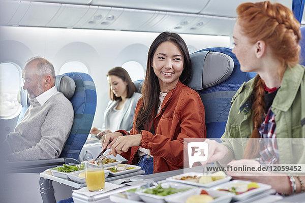 Frauen  die im Flugzeug essen und sich unterhalten