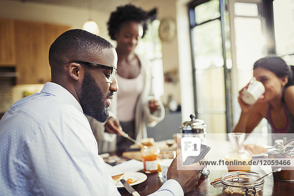Man drinking coffee and texting with smart phone at breakfast table