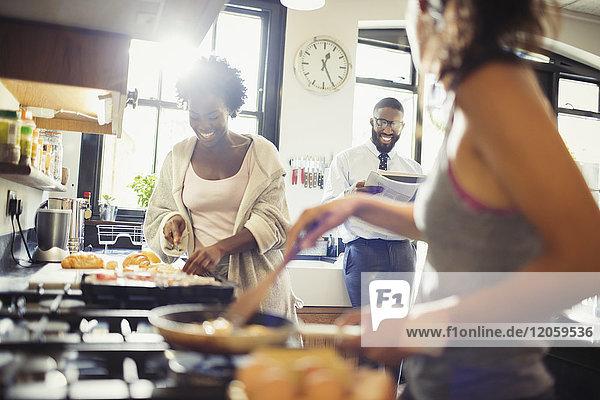 Freundliche Mitbewohner kochen Frühstück in der Küche