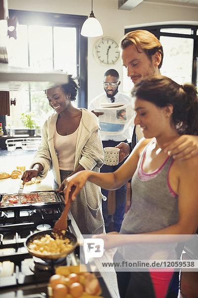 Freund Mitbewohner kochen Rührei am Herd in der Küche
