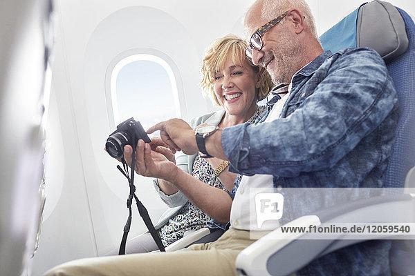 Älteres Ehepaar beim Betrachten von Fotos auf der Digitalkamera im Flugzeug
