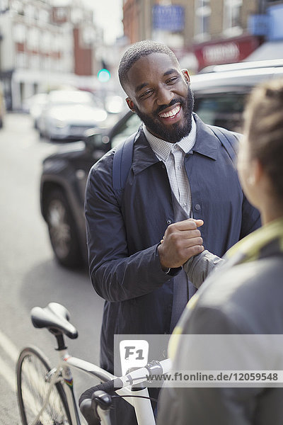 Smiling businessman with bicycle shaking hands with woman on urban street