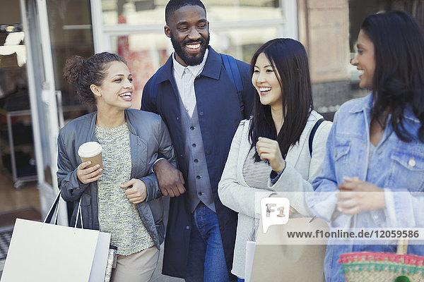 Lächelnde Freunde mit Kaffee und Einkaufstaschen