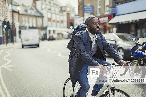 Businessman commuting  riding bicycle on urban street