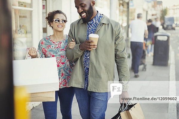Smiling young couple with coffee and shopping bags walking along storefront