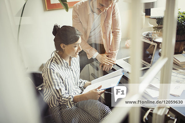 Geschäftsleute  die den Papierkram am Schreibtisch im Büro überprüfen.