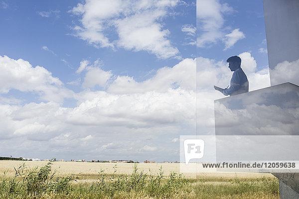Silhouette Geschäftsmann schriftlich auf modernen Balkon mit Blick auf sonnigen blauen Himmel und Wolken