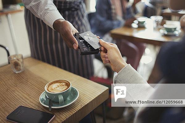 Kunde mit Kreditkartenzahler mit kontaktloser Bezahlung im Cafe