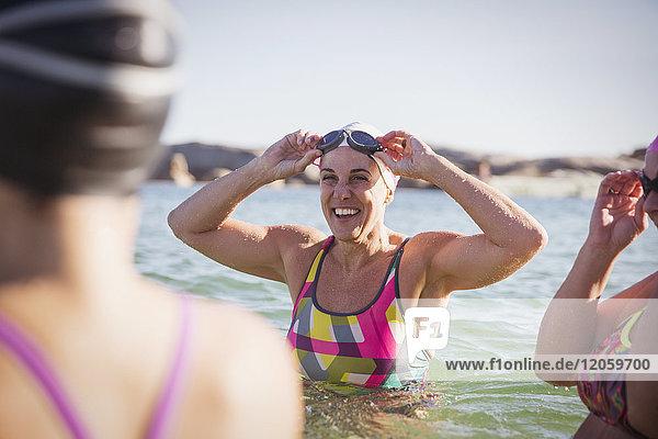 Lächelnde Schwimmerinnen waten im sonnigen Ozean