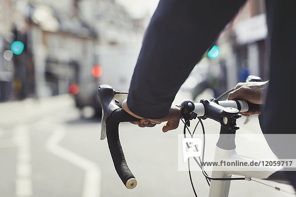 Hands on Man am Fahrradlenker, Pendeln auf sonniger Stadtstraße