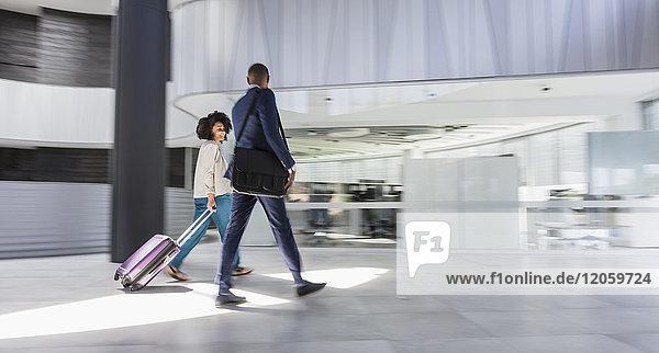 Geschäftsmann und Geschäftsfrau gehen  Koffer ziehen in moderner Bürolobby