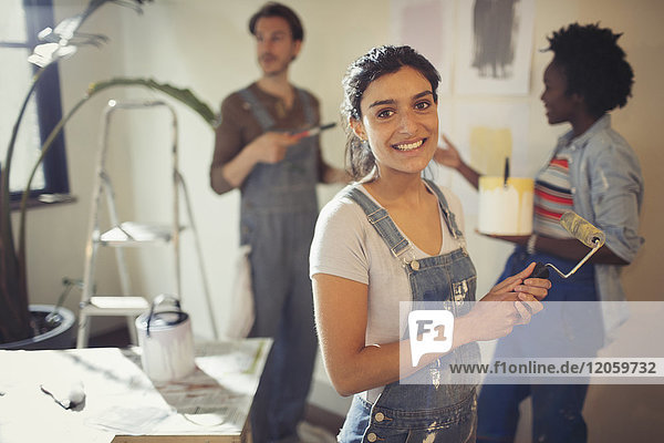 Portrait lächelnde junge Frau beim Malen im Wohnzimmer mit Freunden