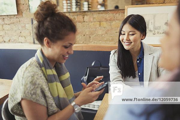 Freundinnen SMS mit Handy im Cafe