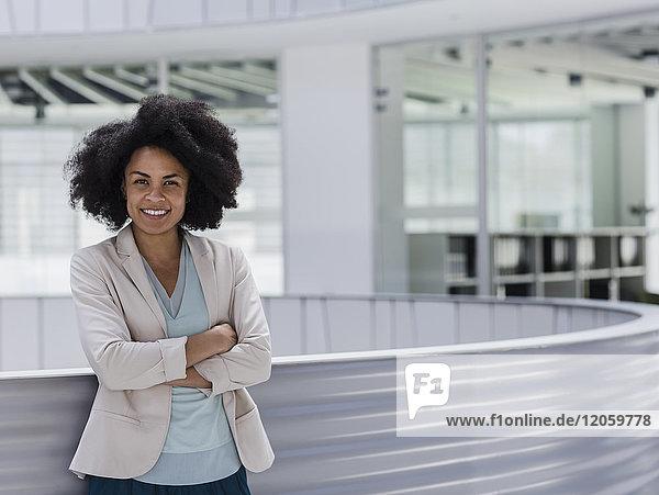 Portrait lächelnde selbstbewusste Geschäftsfrau mit gekreuzten Armen im Büroatrium
