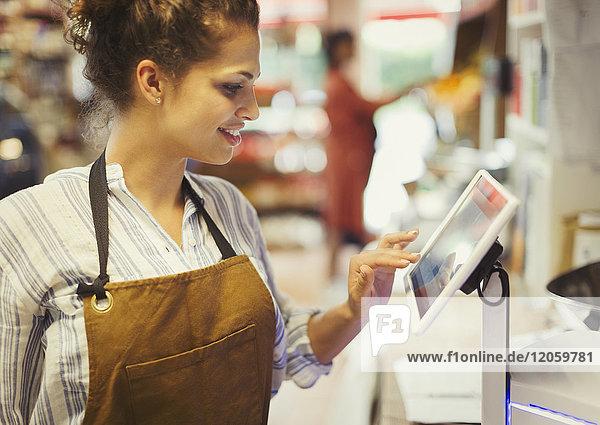 Kassiererin mit Touchscreen-Kasse im Lebensmittelgeschäft