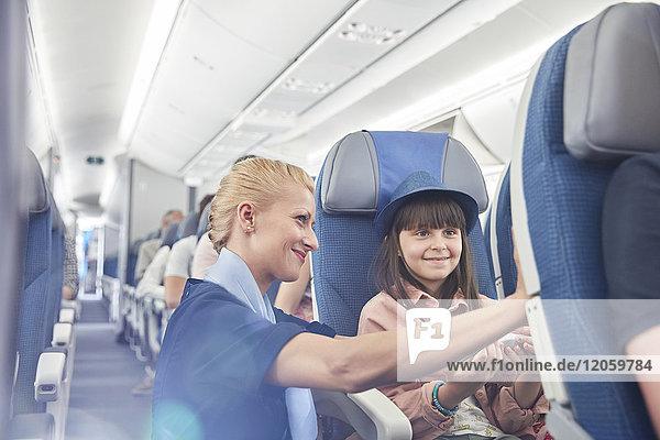 Flugbegleiterin hilft Passagierin im Flugzeug