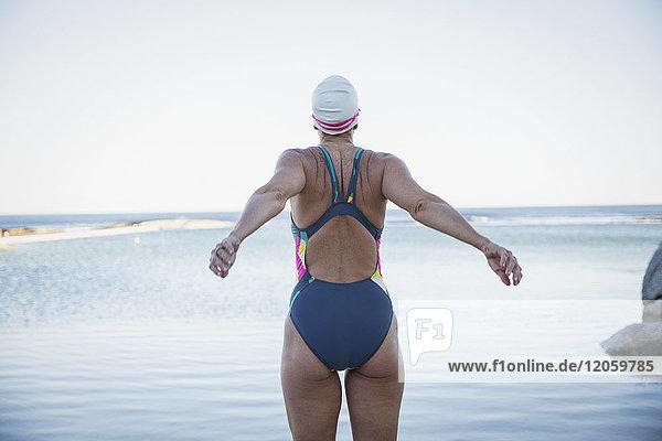 Weibliche Freiwasserschwimmerin, die sich am Meer ausdehnt.
